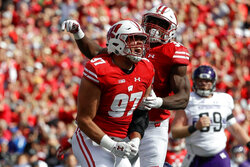 FILE - In this Sept. 30, 2017, file photo, Wisconsin's Isaiahh Loudermilk (97) and Leon Jacobs celebrate after a sack of Northwestern quarterback Clayton Thorson (18) during the first half of an NCAA college football game in Madison, Wis. Wisconsin traditionally wins games primarily because of its running game and defense. Now that Jonathan Taylor has moved on to the NFL, that would seem to put more pressure on the defense to carry the load as the Badgers' offense adjusts to life without the two-time Doak Walker Award winner. The defense looks forward to that challenge.  (AP Photo/Morry Gash, File)