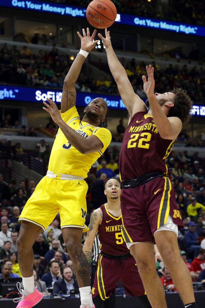 Michigan's Zavier Simpson (3) takes a shot over Minnesota's Gabe Kalscheur (22) during the first half of an NCAA college basketball game in the semifinals of the Big Ten Conference tournament, Saturday, March 16, 2019, in Chicago. (AP Photo/Kiichiro Sato)