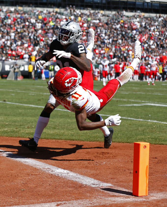 Kansas City Chiefs wide receiver Demarcus Robinson (11) scores a touchdown as Oakland Raiders cornerback Gareon Conley looks on during the first half of an NFL football game Sunday, Sept. 15, 2019, in Oakland, Calif. (AP Photo/D. Ross Cameron)