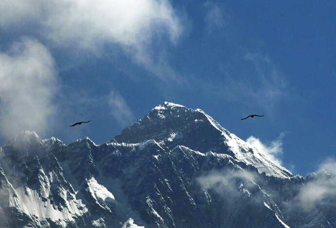 FILE - In this May 27, 2019, file photo, birds fly as Mount Everest is seen from Namche Bajar, Solukhumbu district, Nepal. A Nepal government committee formed after a bad mountaineering season on Mount Everest has recommended new rules that would require climbers to have scaled tall peaks, undergone proper training, and possess certificates of good health and insurance that would cover rescue costs if required. A report by the committee released Wednesday, Aug. 15, says people must have successfully climbed a peak higher than 6,500 meters (21,320 feet) before they can apply for a permit to scale Mount Everest. Each climber would also be required to have a highly experienced guide. (AP Photo/Niranjan Shrestha, File)