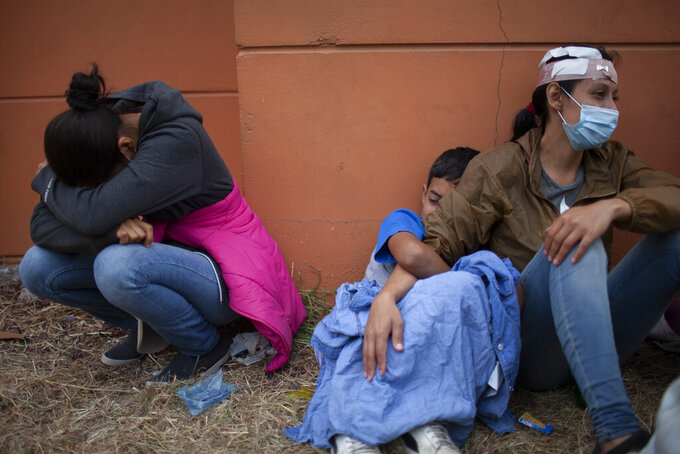 FILE - In this Jan. 17, 2021, file photo injured women, part of a Honduran migrant caravan in their bid to reach the U.S. border, weep as they sit on the side of a highway after clashing with Guatemalan police and soldiers in Vado Hondo, Guatemala, Guatemala. U.S. Federal law allows immigrants facing credible threats of persecution or violence in their home country to seek U.S. asylum. (AP Photo/Sandra Sebastian, File)