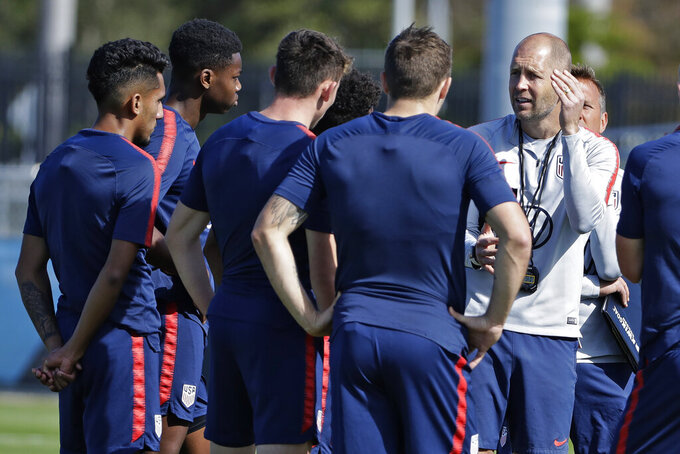 """FILE - In this Wednesday, Jan. 8, 2020, file photo, Gregg Berhalter, right, head coach of the U.S. Men's National Soccer team, instructs some of his players during drills in Bradenton, Fla. The fallout of the coronavirus pandemic could benefit the U.S. soccer team when World Cup qualifying begins in North and Central America and the Caribbean. """"If we go to qualifying in empty stadiums, that's going to change that dynamic considerably, some for the positive and some for the worse,"""" Berhalter said Tuesday, July 21, 2020. (AP Photo/Chris O'Meara, File)"""