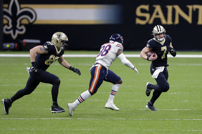 New Orleans Saints quarterback Taysom Hill (7) carries against Chicago Bears strong safety Tashaun Gipson (38) as tight end Josh Hill (89) tries to block in the first half of an NFL wild-card playoff football game in New Orleans, Sunday, Jan. 10, 2021. (AP Photo/Brett Duke)