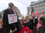 A lawyer holds a effigy with a scull represending a dead lawyer march during a protest against the planned pension change in Paris, Monday, Sept. 16, 2019. French lawyers, doctors, nurses, pilots and others are taking to the streets of Paris to protest planned pension changes by French President Emmanuel Macron's government. Placard read,