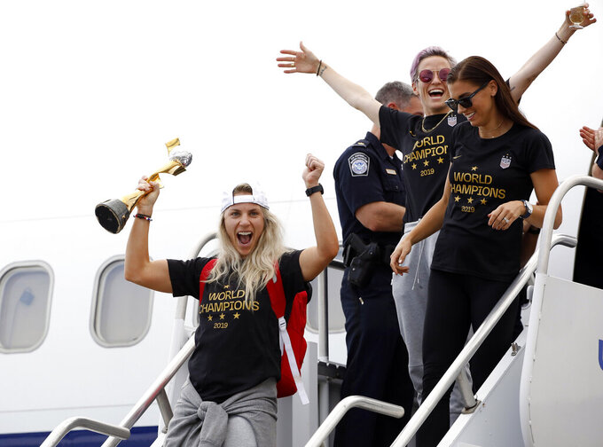 Members of the United States women's soccer team, winners of a fourth Women's World Cup, including Julie Ertz, left, Megan Rapinoe, top center, and Alex Morgan, top right, celebrate after arriving at Newark Liberty International Airport, Monday, July 8, 2019, in Newark, N.J. (AP Photo/Kathy Willens)