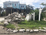 A house is being raised on Ocracoke Island in Ocracoke, N.C., Thursday, June 25, 2020. The secluded travel destination was ravaged by Hurricane Dorian in September and then hit with coronavirus-related travel restrictions in the spring. Residents and business owners are hoping to recoup some of their losses as tourists return, albeit in smaller than usual numbers. (AP Photo/Ben Finley)