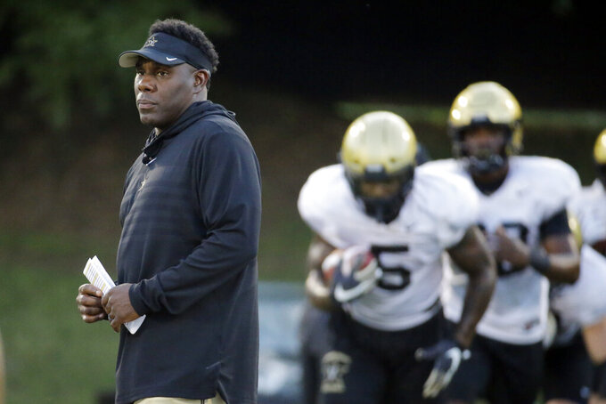 FILE - In this Aug. 5, 2019, file photo, Vanderbilt head coach Derek Mason supervises an NCAA college football practice in Nashville, Tenn. Mason isn't sharing who Vanderbilt's new starting quarterback will be before the season opener. The coach needs every advantage he can get with the Commodores hosting No. 3 Georgia for their season opener. (AP Photo/Mark Humphrey, File)