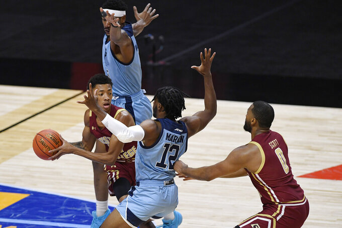 Boston College's Kamari Williams, left, looks to pass to Frederick Scott, right, as Rhode Island's Antwan Walker, top, and Malik Martin, center, defend during the first half of an NCAA college basketball game Thursday, Nov. 26, 2020, in Uncasville, Conn. (AP Photo/Jessica Hill)