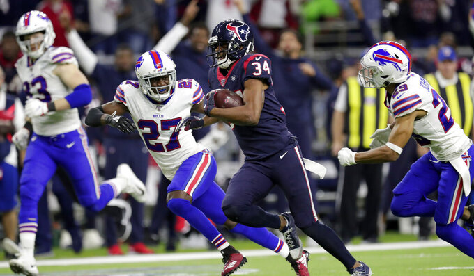 Houston Texans running back Taiwan Jones (34) catches a pass and runs for a first down as Buffalo Bills' Tre'Davious White (27) and Kevin Johnson (29) defend during overtime of an NFL wild-card playoff football game Saturday, Jan. 4, 2020, in Houston. (AP Photo/Michael Wyke)
