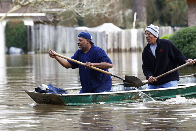 Jackson, Miss., homeowners use shovels to work their way through Pearl River floodwater in this Jackson, Miss., neighborhood Sunday, Feb. 16, 2020. Residents of Jackson braced Sunday for the possibility of catastrophic flooding in and around the Mississippi capital as the Pearl River rose precipitously after days of torrential rain. (AP Photo/Rogelio V. Solis)