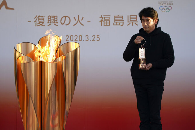 "An official holds a lantern containing the Olympic Flame at the end of a flame display ceremony in Iwaki, northern Japan, Wednesday, March 25, 2020. IOC President Thomas Bach has agreed ""100%"" to a proposal of postponing the Tokyo Olympics for about one year until 2021 because of the coronavirus outbreak. (AP Photo/Eugene Hoshiko)"
