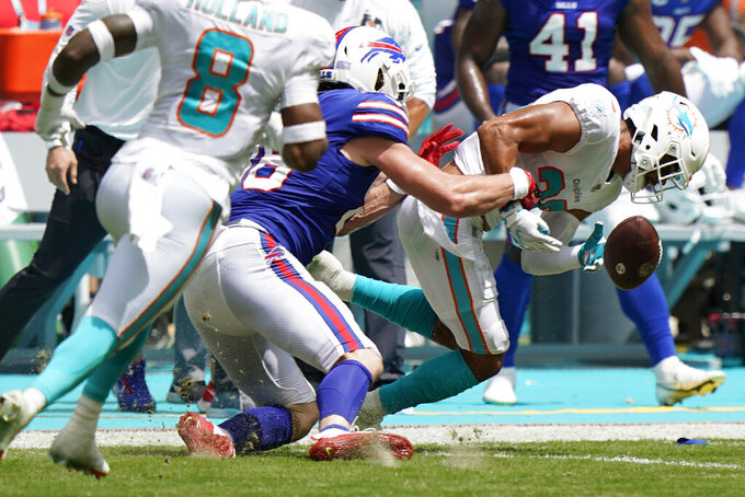 Buffalo Bills tight end Dawson Knox (88), center, tackles Miami Dolphins safety Brandon Jones (29), during the first half of an NFL football game, Sunday, Sept. 19, 2021, in Miami Gardens, Fla. (AP Photo/Wilfredo Lee)