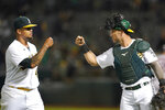 Oakland Athletics pitcher Frankie Montas, left, is greeted by catcher Yan Gomes as they walk off the field during the sixth inning of a baseball game against the Houston Astros in Oakland, Calif., Friday, Sept. 24, 2021. (AP Photo/Jeff Chiu)