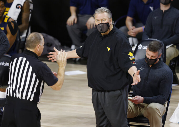 West Virginia head coach Bob Huggins talks with an official during the second half of an NCAA college basketball game, Tuesday, Feb. 2, 2021, in Ames, Iowa. West Virginia won 76-72. (AP Photo/Matthew Putney)