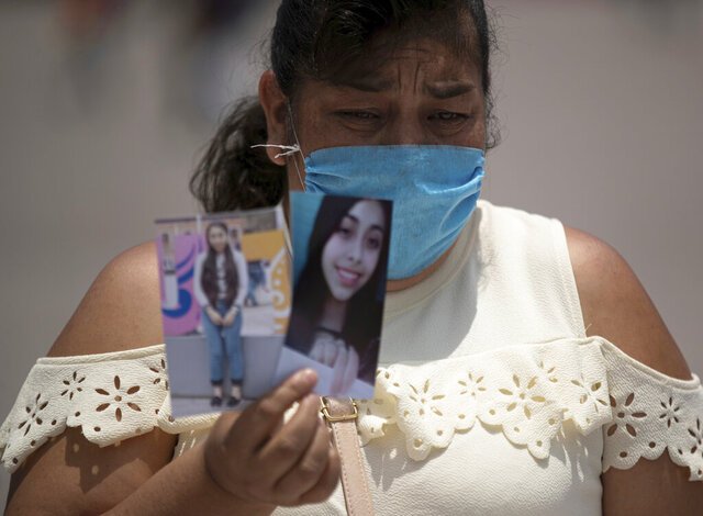 FILE - In this Aug. 5, 2020 file photo, Maria Alberto holds up photos of her missing daughter Montserrat Murrieta, during a protest to call attention to the country's thousands of disappeared, at Mexico City's main square the Zocalo. (AP Photo/Fernando Llano, File)