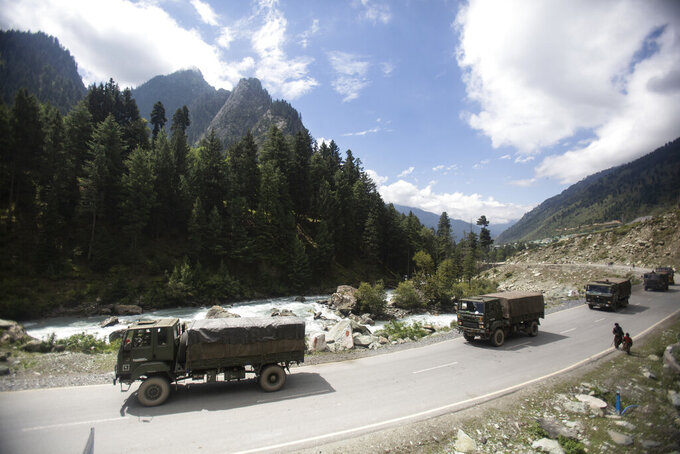 FILE - In this Tuesday, Sept. 1, 2020, file photo, an Indian army convoy moves on the Srinagar- Ladakh highway at Gagangeer, northeast of Srinagar, Indian-controlled Kashmir. As the escalating and bitter military standoff between India and China protracts following their bloodiest confrontation in decades in the Ladakh region in 2020, experts warn the two nuclear-armed countries can unintentionally slide into a war over the roof of the world. The two most populous nations share thousands of kilometers (miles) disputed border and have accused each other for opening new fronts. (AP Photo/Mukhtar Khan)
