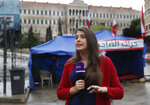 "In this Thursday, Dec. 5, 2019 photo, Rima Hamdan, a Lebanese reporter for OTV a station that is backed by Lebanese President Michel Aoun, reports from a square where anti-government protesters hold ongoing protests, in downtown Beirut, Lebanon. ""The protest movement has turned our lives upside down,"" said Hamdan, who during one of her reports slapped a man on his hand after he pointed his middle finger to her. She said the station's logo ""is our identity even though sometimes we had to remove it for our own safety."