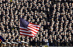 FILE - In this Dec. 1, 2001, file photo, the American flag flies with a background of Navy midshipmen during the national anthem at the 102nd Army Navy NCAA college football game in Philadelphia. (AP Photo/Chris Gardner, File)