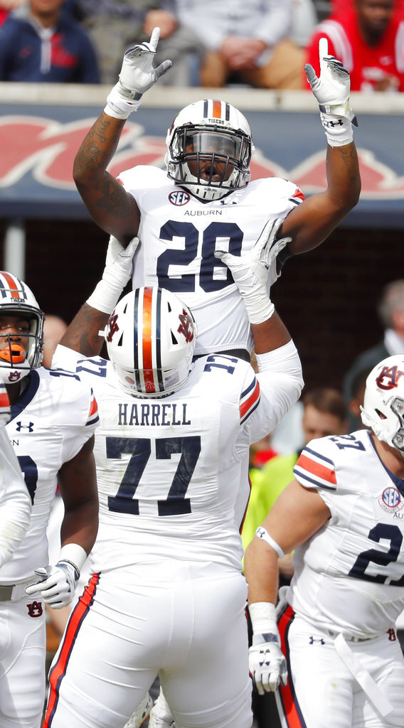 Auburn offensive lineman Marquel Harrell (77) lifts running back JaTarvious Whitlow (28) after Whitlow scored on a 3-yard touchdown pass during the first half of an NCAA college football game against Mississippi on Saturday, Oct. 20, 2018, in Oxford, Miss. (AP Photo/Rogelio V. Solis)