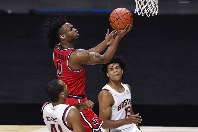 St. John's Posh Alexander, top, goes up for a basket as Boston College's Steffon Mitchell, left, and DeMarr Langford Jr., right, defend, in the first half of an NCAA college basketball game, Monday, Nov. 30, 2020, in Uncasville, Conn. (AP Photo/Jessica Hill)
