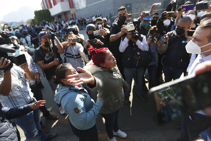 A woman demands information from a lawmaker of people injured when a metro overpass collapsed, near the site of the wreckage in Mexico City, Tuesday, May 4, 2021. The elevated section of the metro's Line 12 collapsed late Monday killing at least 23 people and injuring at least 79, city officials said. (AP Photo/Fernando Llano)