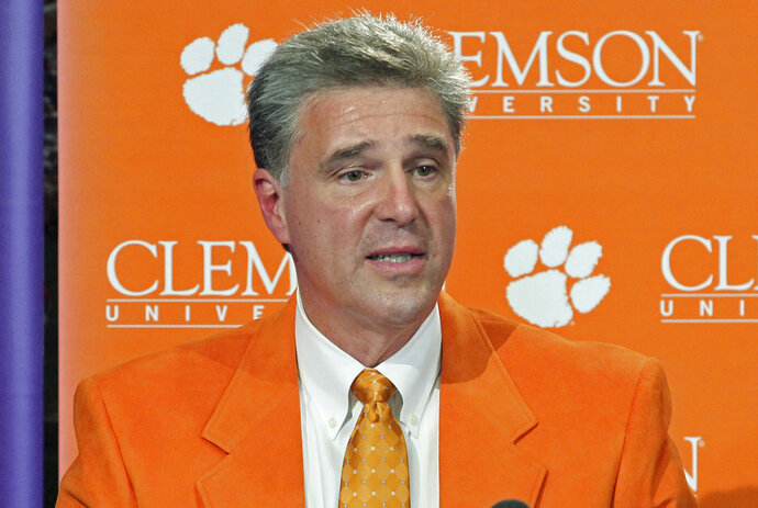 FILE - In this Oct. 29, 2012, file photo, Dan Radakovich answers a question after being introduced as Clemson's new athletic director in Clemson, S.C. Second-ranked Clemson is the only major conference school in the Carolinas and Virginia largely that will play its scheduled football game this weekend as Hurricane Florence looms. Clemson officials say they are monitoring the storm's path and believe there were be no issues playing the Saturday's game against Georgia Southern. Clemson has moved up the start time to noon EST from the original 3:30 p.m. kickoff. (Mark Crammer/The Independent-Mail via AP)