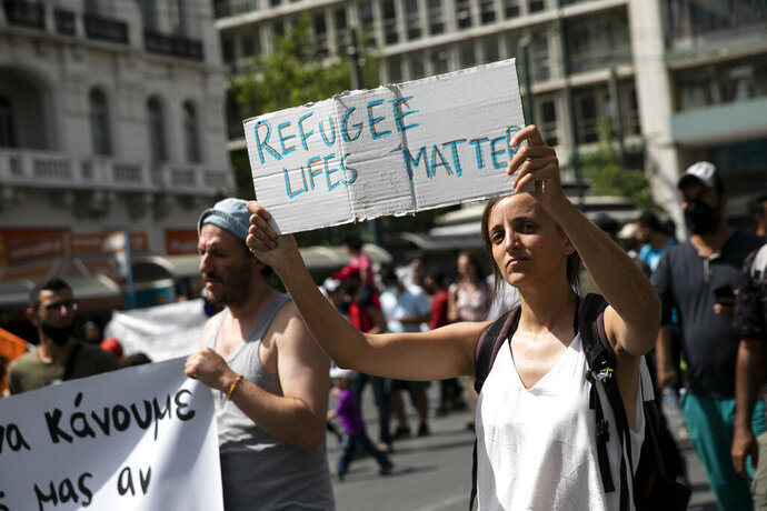 Protesters take part in a rally in favor of migrants who live in Greece, in Athens, on Saturday, June 20, 2020. Some hundreds of protesters marched against the possible discontinuation of a migrants' housing program which will leave thousands without a place to stay. (AP Photo/Yorgos Karahalis)