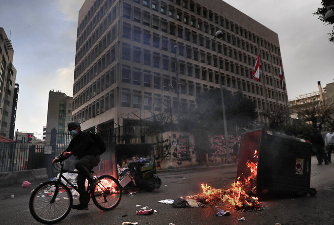 A man rides his bicycle past garbage containers set on fire by protesters blocking a main road in front the Lebanese Central Bank building, background, in Beirut, Lebanon, Monday, March 22, 2021. Protesters blocked some roads in the Lebanese capital with burning tires Monday after talks on the formation of a new Cabinet broke down, heralding more economic and financial collapse for the small Arab country. (AP Photo/Hussein Malla)