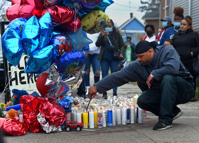A man lights candles at a vigil for Randell Jones on Monday, April 12, 2021 in Hartford.  Police said Randell Jones, 3, was riding in a car with his mother, other relatives and a man when another vehicle pulled along side them and someone opened fire on Saturday. Randell died in the shooting, which appeared to have targeted the man in the car, police said. (Brad Horrigan /Hartford Courant via AP)