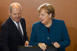 German Chancellor Angela Merkel, right, and Social Democratic Vice Chancellor and Finance Minister Olaf Scholz arrives for the weekly cabinet meeting of the German government at the chancellery in Berlin, Germany, Wednesday, Nov. 6, 2019. (AP Photo/Markus Schreiber)