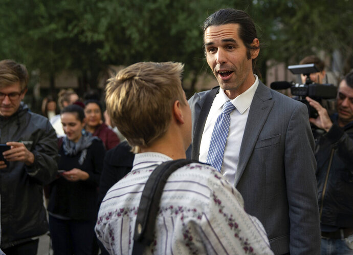 Border aid volunteer Scott Warren talks with friends and supporters outside the Federal Courthouse, Wednesday, Nov. 20, 2019 in Tucson, Ariz. Warren was acquitted Wednesday on charges he illegally harbored two Central American immigrants at a camp in southern Arizona operated by a humanitarian group. (Josh Galemore/Arizona Daily Star via AP)