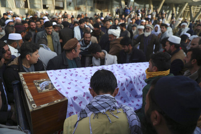 CORRECTS DATE OF ATTACK AND IDENTIFIES RASHEED AS THE HEAD OF THE INDEPENDENT ELECTIONS WATCHDOG -- Afghans carry the coffin of Mohammad Yousuf Rasheed, executive director of the non-governmental Free and Fair Election Forum of Afghanistan, during his funeral ceremony, in Kabul, Afghanistan, Wednesday, Dec. 23, 2020. Separate bombing and shooting attacks in Afghanistan's capital left several people dead Wednesday, including Rasheed, the head of the independent elections watchdog, officials said. (AP Photo/Rahmat Gul)