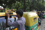 An auto-rickshaw driver puts up off duty board during a public transport strike in New Delhi, India, Thursday, Sept. 19, 2019. Commuters in the Indian capital are facing problems as a large section of the public transport, including private buses, auto-rickshaws and a section of app-based cabs Thursday remained off the roads in protest against a sharp increase in traffic fines imposed by the government under a new law.(AP Photo/Manish Swarup)