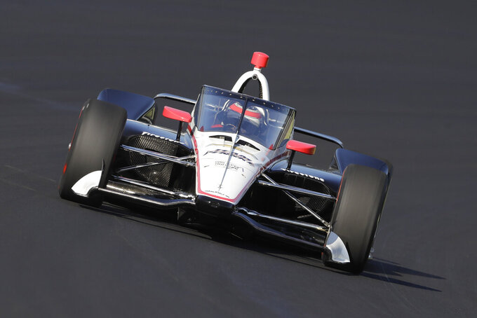FILE - In this Oct. 2, 2019, file photo, Will Power, of Australia, drives into turn one during Aeroscreen testing at Indianapolis Motor Speedway in Indianapolis. The 2020 IndyCar season will open Saturday night, June 6, 2020, at Texas Motor Speedway. The race will also mark the official race debut of the safety innovation for enhanced driver cockpit protection. The safety feature is a ballistic, canopy-like windscreen anchored by titanium framework encompassing the cockpit.  (AP Photo/Darron Cummings, File)