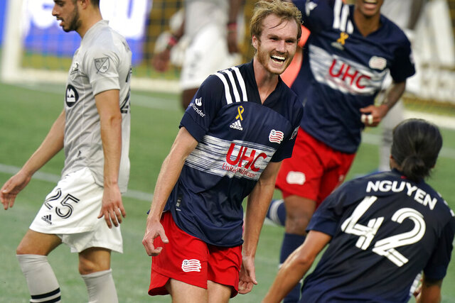 New England Revolution's Henry Kessler, center, celebrates with teammate Lee Nguyen, right, after scoring in the first half of an MLS soccer match as Montreal Impact's Emanuel Maciel (25) steps away, Wednesday, Sept. 23, 2020, in Foxborough, Mass. (AP Photo/Steven Senne)