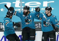 San Jose Sharks defenseman Brent Burns, center, celebrates with teammates Patrick Marleau (12) and Mario Ferraro (38) after scoring a goal against Minnesota Wild during the first period of an NHL hockey game in San Jose, Calif., Monday, Feb. 22, 2021. (AP Photo/Tony Avelar)