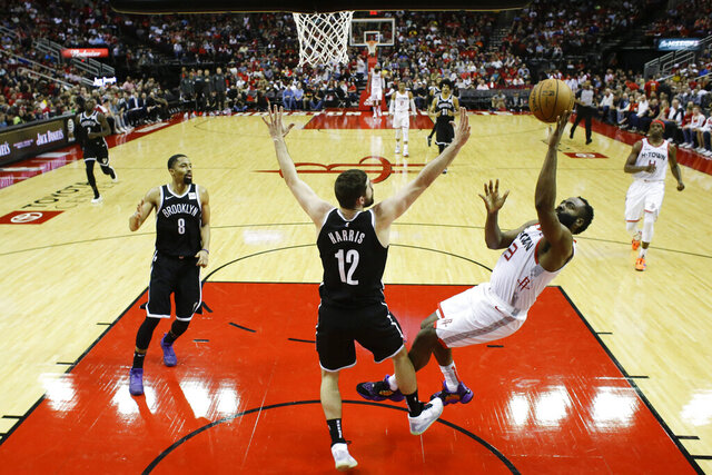 Houston Rockets guard James Harden, right, shoots as Brooklyn Nets guard Joe Harris (12) defends during the second half of an NBA basketball game Saturday, Dec. 28, 2019, in Houston. (AP Photo/Eric Christian Smith)