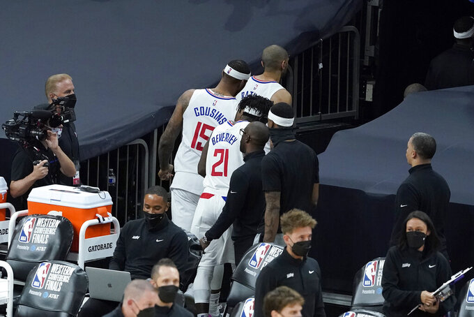 Los Angeles Clippers forward Nicolas Batum, top, walks through a tunnel in front of center DeMarcus Cousins (15) and guard Patrick Beverley (21) after the Phoenix Suns defeated the Clippers in Game 2 of the NBA basketball Western Conference Finals, Tuesday, June 22, 2021, in Phoenix. (AP Photo/Matt York)