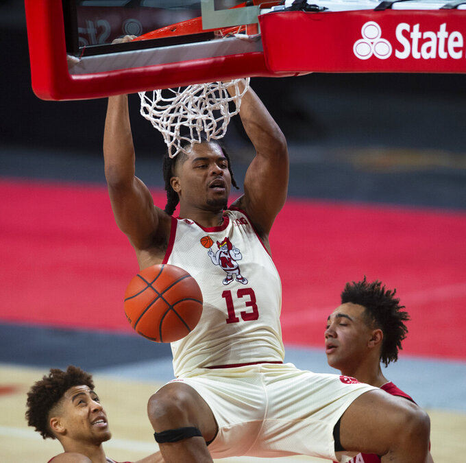 Nebraska's Derrick Walker dunks the ball over Indiana defenders in the second half of an NCAA college basketball game Sunday, Jan. 10, 2021, in Lincoln, Neb. (Kenneth Ferriera/Lincoln Journal Star via AP)