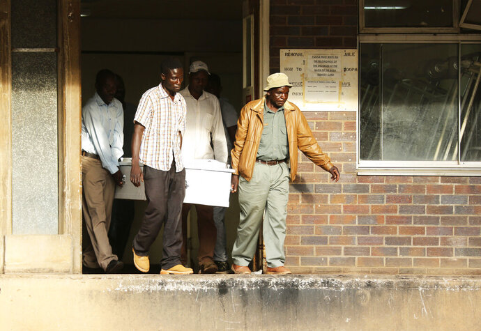 In this Jan. 9, 2019, photo, a family collects the body of their son who died at Parirenyatwa Hospital in Harare, Zimbabwe. The family who blamed the death of their son on the doctors strike said they were devastated. A doctors strike in Zimbabwe has crippled a health system that was already in intensive care from neglect. It mirrors the state of affairs in a country that was full of promise a year ago with the departure of longtime leader Robert Mugabe but now faces economic collapse.(AP Photo/Tsvangirayi Mukwazhi)