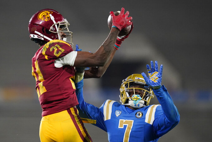Southern California wide receiver Tyler Vaughns, left, catches a pass while defended by UCLA defensive back Mo Osling III (7) during the fourth quarter of an NCAA college football game Saturday, Dec 12, 2020, in Pasadena, Calif. (AP Photo/Ashley Landis)