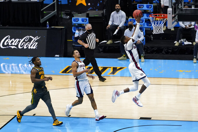 Gonzaga guard Joel Ayayi drives to the basket ahead of teammate guard Jalen Suggs (1) and Baylor guard Davion Mitchell (45) during the first half of the championship game in the men's Final Four NCAA college basketball tournament, Monday, April 5, 2021, at Lucas Oil Stadium in Indianapolis. (AP Photo/Darron Cummings)