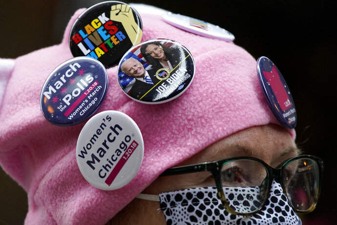 A woman wears a hat with button badges as she attends the Women's March in downtown Chicago, Saturday, Oct. 17, 2020.  Dozens of Women's March rallies were planned from New York to San Francisco to signal opposition to President Donald Trump and his policies, including the push to fill the seat of late Supreme Court Justice Ruth Bader Ginsburg before Election Day. (AP Photo/Nam Y. Huh)