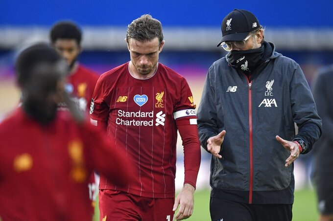 Liverpool's manager Jurgen Klopp and Liverpool's Jordan Henderson leave the field at the end of the English Premier League soccer match between Everton and Liverpool at Goodison Park in Liverpool, England, Sunday, June 21, 2020. (Peter Powell/Pool via AP)