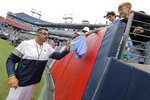 Tennessee Titans head coach Mike Vrabel, left, gives autographs to fans before NFL football training camp in Nissan Stadium, Saturday, Aug. 3, 2019, in Nashville, Tenn. The Titans have had trouble filling their stadium for years and have needed the help of visiting fans to sell as many seats as they have. (AP Photo/Mark Humphrey)