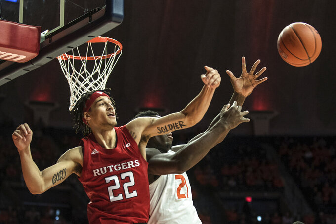 Rutgers' Caleb McConnell (22) bats the ball away from Illinois' Kofi Cockburn in the first half of an NCAA college basketball game, Sunday, Jan. 11, 2020, in Champaign, Ill. (AP Photo/Holly Hart)