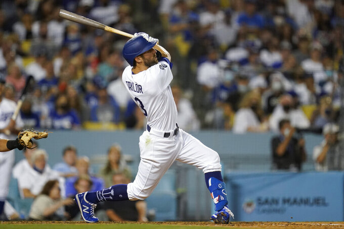 Los Angeles Dodgers' Chris Taylor hits a sacrifice fly to left field during the fourth inning of a baseball game against the San Diego Padres Friday, Sept. 10, 2021, in Los Angeles. Will Smith scored. (AP Photo/Ashley Landis)