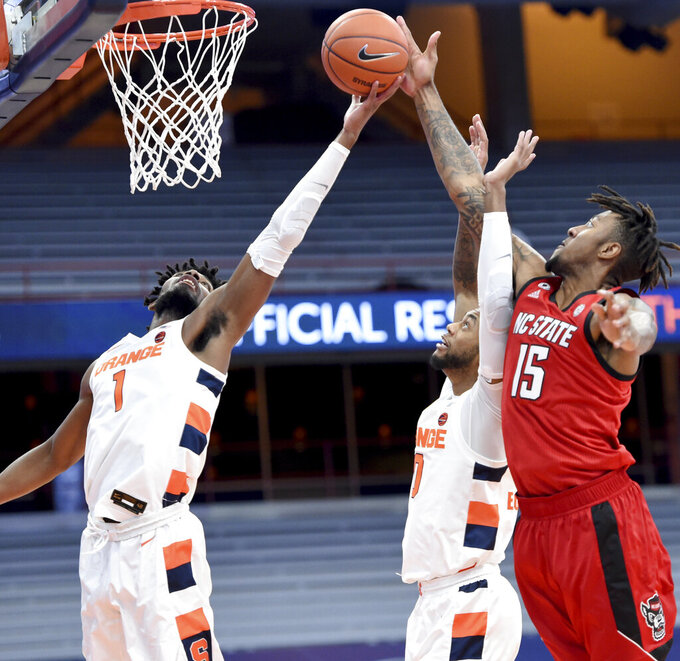 Syracuse forwards Quincy Guerrier (1), and Alan Griffin (0) battle North Carolina State forward Manny Bates (15) for a rebound during an NCAA college basketball game Sunday, Jan. 31, 2021,  in Syracuse, N.Y. (Dennis Nett/The Post-Standard via AP)