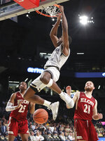 Georgia Tech forward Moses Wright dunks over Elon forward Hunter Woods, left, and guard Andy Pack during an NCAA college basketball game, Monday, Nov. 11, 2019, in Atlanta. (Curtis Compton/Atlanta Journal-Constitution via AP)