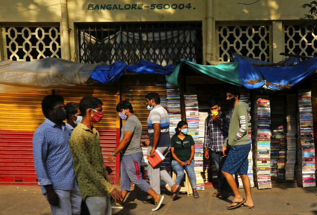 Indians wearing face masks as prevention against the coronavirus walk past a roadside bookshop in Bengaluru, India, Tuesday, May 26, 2020. For a seventh consecutive day India reported a record single-day jump in new virus cases. India has been easing its lockdown, with domestic flights resuming Monday at a fraction of normal. (AP Photo/Aijaz Rahi)